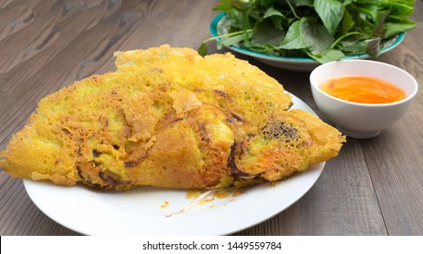 Vietnamese crepe or sizzling pancake (banh xeo): Rice flour mixed with coconut milk into batter. Fried batter in thin shape with spring onions & topping: cooked shrimp, pork belly, wrap with vegetable