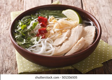 Vietnamese cuisine: soup Pho Ga with chicken, rice noodles and fresh herbs in a bowl close-up. Horizontal