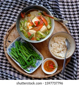 Vietnamese daily meal for lunch, vegan food menu with boiled peas, bowl of okra, tomato, tofu soup and rice on tray, ready to eat