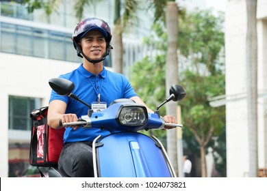 Vietnamese delivery man riding on scooter
