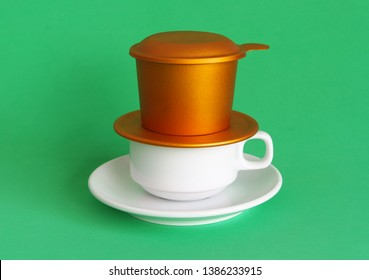 Vietnamese drip coffee, coffee cup and metallic phin on green background