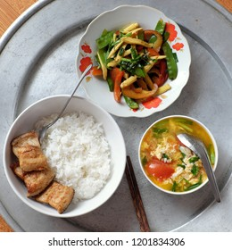 Vietnamese family daily meal for lunch with cooked rice, fried vegetable, fried fish and egg soup with tomato, simple homemade food but  nutrition and safe