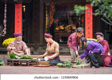 Vietnamese family members making Banh Chung together on old-styled house yard. Chung cake is a very well-known dish that could never miss on the altar, and family meal of Vietnamese during Tet holiday