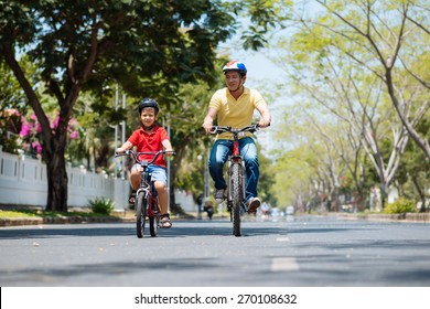 Vietnamese father and son riding on bicycles together
