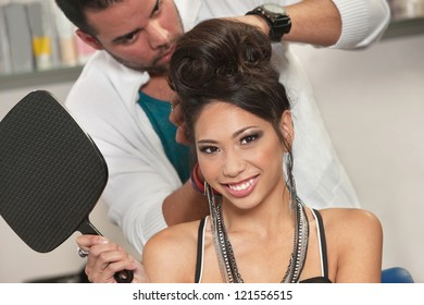 Vietnamese female holding mirror with hairdresser working behind her