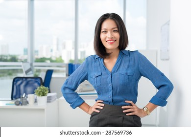 Vietnamese female manager with hands on hips looking at camera
