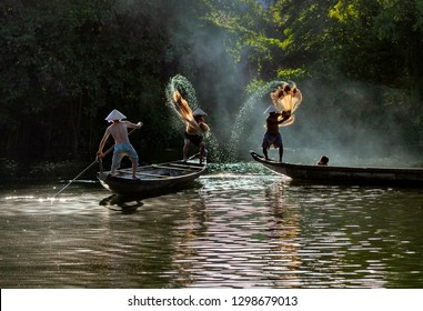 Vietnamese fishermen throw a fishing nets for they start catching fish in the river. Morning view. Hue city, Vietnam