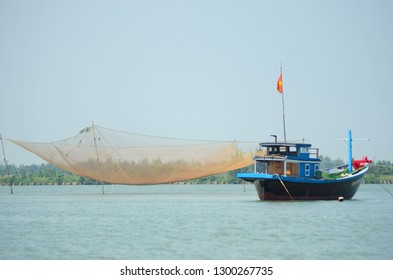 A Vietnamese fishing boat is moored beside a fishing net. This net is suspended on poles above the water. A headland is in the distance. The sky is blue.