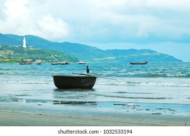 Vietnamese fishing boats near a beach, with a basket-shaped boat resting on the sand. In the background are some hills, with a giant white Buddha statue overlooking the bay. The sky is overcast.