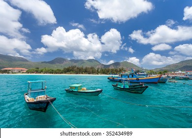 Vietnamese fishing boats on a tropical Con Dao Island. View from the pier in the direction of a beach with white sand.