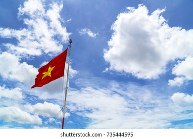 Vietnamese flag flying under the blue cloudy sky