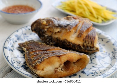 Vietnamese food for daily meal, fried fish with mango and fish sauce, titapia fish or saint peter fish fry is delicious eating