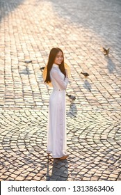 Vietnamese girl dressed Ao Dai white dress. Vietnamese traditional dress. Asian Beautiful girl walking in the city at sunrise.