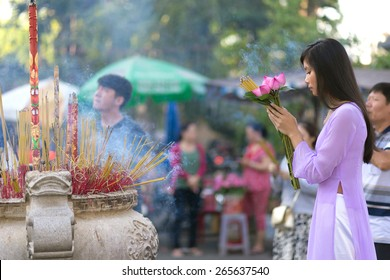 Vietnamese girl praying in Buddhist temple, holding lotus flowers, Saigon, Vietnam
