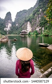 Vietnamese Girl with straw hat in Trang An Scenic Landscape (UNESCO World Heritage Site). It's Halong Bay on land of Vietnam. Ninh Binh province, Vietnam.
