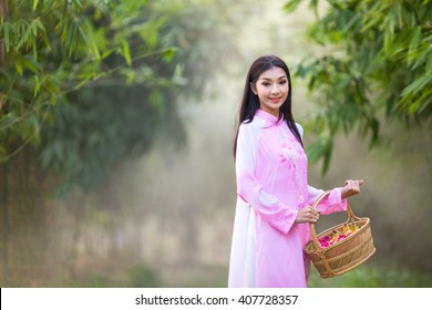Vietnamese girl traditional dress holding a basket , Ao dai is famous traditional costume for woman in Vietnam