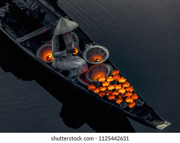 Vietnamese girls set fire to ritual lanterns, which they send to sail on the river at night to urge luck. Bridge survey. Hue city. Vietnam