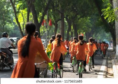 Vietnamese girls wear traditional long dress Ao Dai cycling on Hanoi street