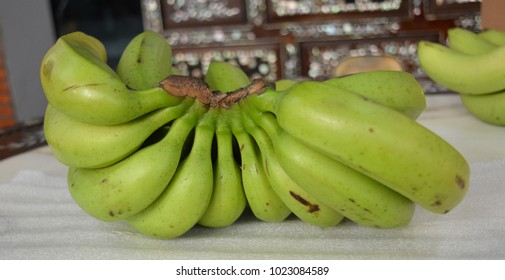 Vietnamese green banana on table, isolated on white background