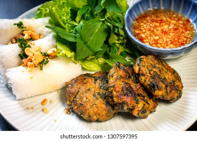 Vietnamese grilled fish cakes with dill (Cha Ca) appetizer garnished with spicy sauce, green salad, fresh vermicelli, peanut