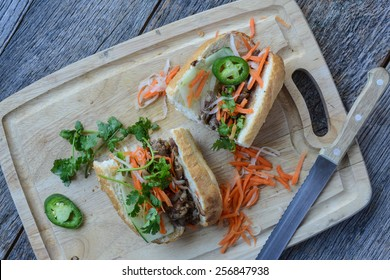 Vietnamese Grilled Pork Banh Mi Sandwich on Rustic Wood Background