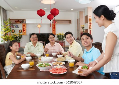 Vietnamese happy big family celebrating Tet together; couplets with best wishes for coming year in the background