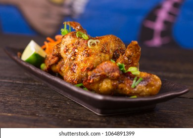 Vietnamese honey glazed chicken wings on wooden table and colorful background  perspective