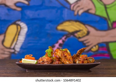 Vietnamese honey glazed chicken wings on wooden table and colorful background front view
