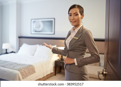 Vietnamese hotel customer service representative showing double room