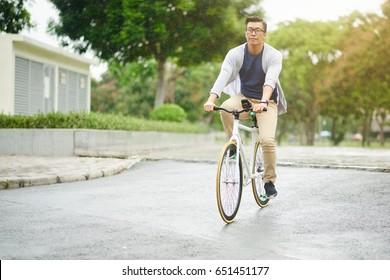 Vietnamese man in glasses riding bicycle on rainy day