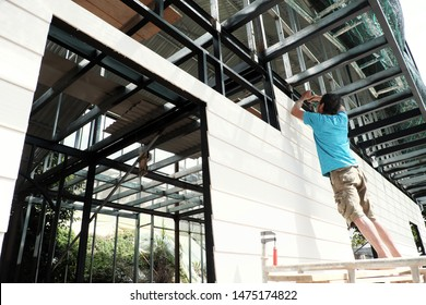 Vietnamese man stand on scaffold and shoot screw on smart wood panel to iron house frame, male do it yourself a house, Da Lat, Viet Nam