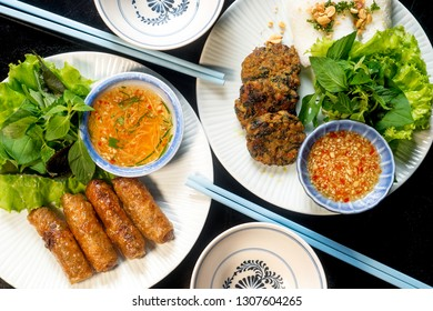 Vietnamese meal: grilled fish cakes with dill (Cha Ca) and Fried Spring rolls. Appetizer with spicy sauce, green salad, fresh vermicelli, peanut on black background