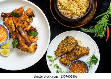 Vietnamese meal: grilled turmeric fish with dill (Cha ca La vong) and fish sauce, Honey chicken baked dotted with lime chilli salt, fried rice with sea food in claypot on black background