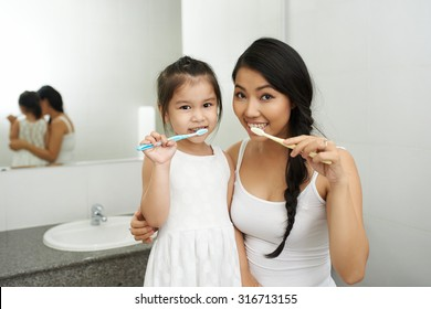 Vietnamese mother and daughter brushing teeth together