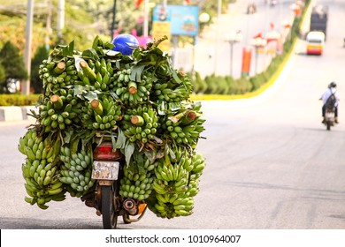 Vietnamese motorbike drivers overloaded by green bananas