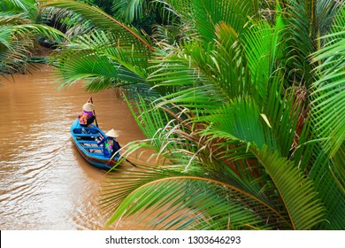 Vietnamese old women on traditional boat paddling by yellow brown water in canal. Mekong river delta - popular travel destination for day tour during vacation in Saigon ( Ho Chi Minh ) city, Vietnam.