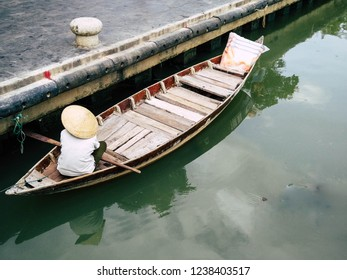 Vietnamese paddler waiting for tourists in wood traditional boat. Hoi An, Vientnam