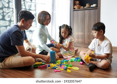 Vietnamese parents and children sittig on floor in living room and playing with plastic toys and blocks