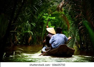 vietnamese people paddling in the Mekong river, Vietnam