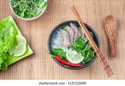 Vietnamese Pho Bo soup on a bamboo Mat with herbs. Top view.