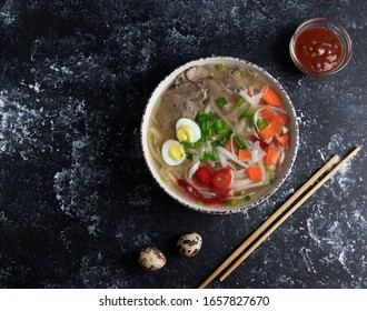 vietnamese pho broth, spicy asian noodle soup with quail eggs and spicy red sauce and wooden chopsticks, flat lay