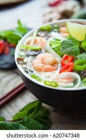 Vietnamese Pho Tom  Rice Noodles Soup with King Prawns. Asian cuisine cooking spices: ginger, lime, chili, garlic, spring onions,lemon grass,  chives, shallots, mint and Shiitake mushrooms.