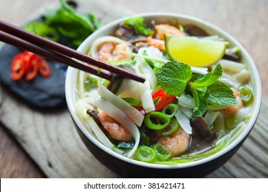 vietnamese pho tom yum -  asian soup with prawns rice noodles lime shiitake mushrooms fresh mint chilli spring onions  and sweet basil