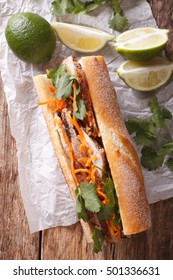 Vietnamese Pork Banh Mi Sandwich with Cilantro and carrot close-up on the table. vertical view from above