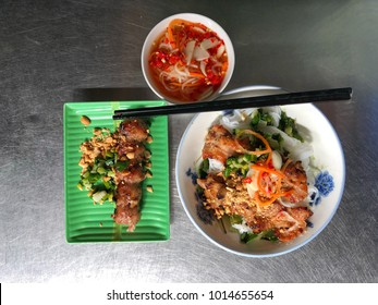 Vietnamese rice noodle with grilled pork and fried spring rolls with red chilli vegetables and condiments and dipping sauce on metal table top