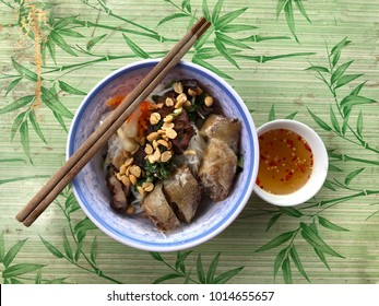 Vietnamese rice noodle with grilled pork and fried spring rolls with red chilli vegetables and condiments and dipping sauce on old table top