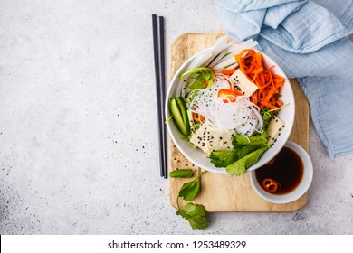 Vietnamese rice noodle with tofu and chilli vegetables salad in white bowl, top view, copy space.