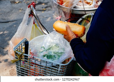 Vietnamese sandwich or Banh Mi Thit sell on street. Stock photo of Vietnamese pork sandwich is popular street food in Vietnam. Woman make and sell bread with pork, pate,egg, carrot, chilli, cilantro