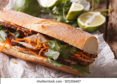 Vietnamese sandwich with cilantro and carrot close-up on the table. horizontal