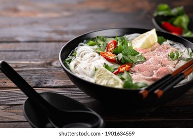 Vietnamese soup Pho Bo with beef and noodles on a wooden background, selective focus